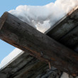 Stock Photo: Wooden roof, drooping snow 2