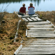 Two girls sit on pier — Stock Photo #2495006