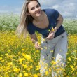 Beautiful girl in field with flower — Stock Photo