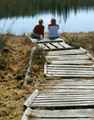 Two girls sit on pier — Stockfoto