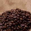 Coffe beans with focus on burlap fabric — Stock Photo #2386395