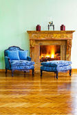 Blue armchair fireplace — Stock Photo