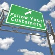 Freeway Sign - Follow Your Customers - Stock Photo
