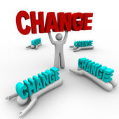 One Stands Holding Change, Others Crushed — Stock Photo
