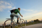 Bike Messenger in front of a City — Stock Photo