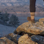 Hiker or trail runner legs on rock — Stock Photo