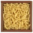 Uncooked fusilli pasta in wooden box — Stock fotografie