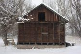 Old, small barn iduring snow storm — Stock Photo