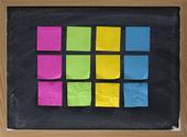 Blank sticky notes on blackboard — Stock Photo