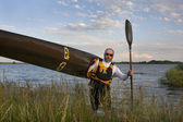 Paddler carrying a racing kayak — Stock Photo