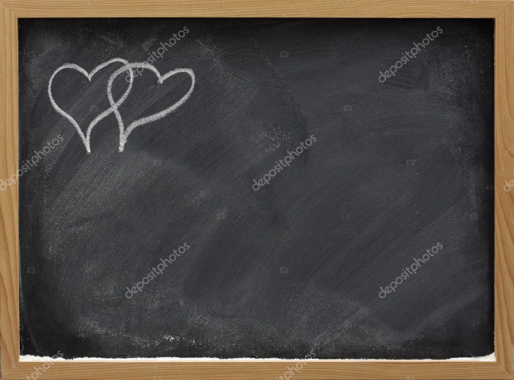 Blackboard in wooden frame with eraser smudges and two interlaced hearts sketched with white chalk in a corner, copy space — Stock Photo #2050718