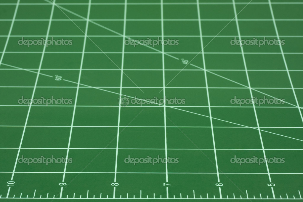 Green self healing cutting mat with grid of white converging lines, focus on inch ruler in front — Stock Photo #2053792