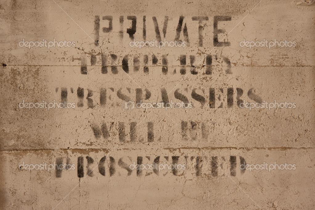 Faded private property, trespassers will be prosecuted sign painted on a concrete wall   Stock Photo #2056133