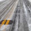 Slippery icy road with yellow line - Stock Photo