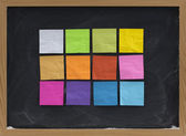 Colorful sticky notes on blackboard — Stock Photo