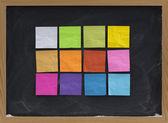 Colorful sticky notes on blackboard — Stock Photo