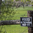 No trespassing sign on a fence surrounding green - Stock Photo
