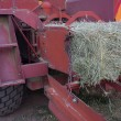 Square bale of hay coming out of farm machinery — Stock Photo