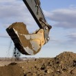 Excavator arm and scoop digging dirt — Stock Photo