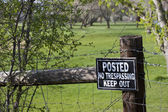 No trespassing sign on a fence surrounding green — Stock Photo