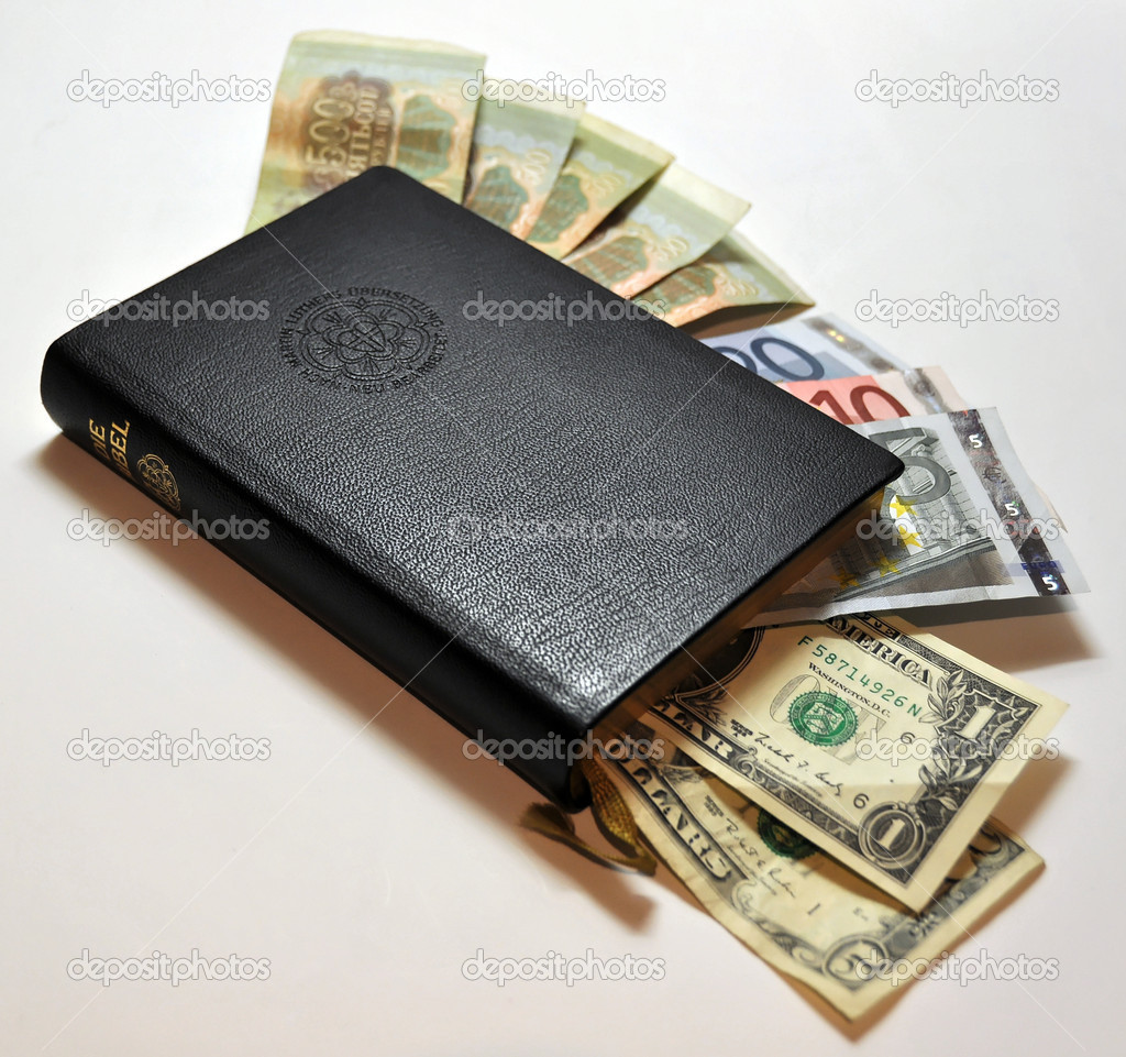 Black leather bible with money (Dollars, Euro, Rubles) poking out on white background — Stock Photo #2047650
