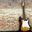 Foto de Stock  : Guitar leaning against wall