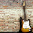 Stock fotografie: Guitar leaning against wall