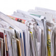 Vertical pile of newspapers and flyers - Stock Photo