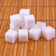Bunch of white sugar cubes on placemat - Stock Photo