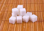 Bunch of white sugar cubes on placemat — Stock Photo