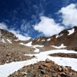 Rocks, snow, sky and clouds in mountains — Stock Photo