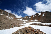 Rocks, snow, sky and clouds in mountains — Стоковое фото