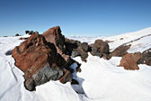 Rocks in snow against a clear blue sky — Stock Photo