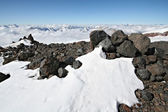Stones in snow against clear blue sky and mountains in Caucasus — Stock Photo