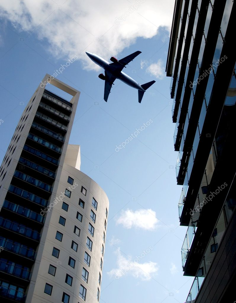 Jet passenger aircraft flies over tower blocks — Stock Photo #2503392