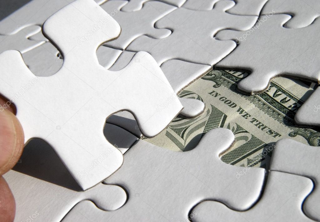 Fingers holding jigsaw piece revealing US Dollar — Stock Photo #2503408