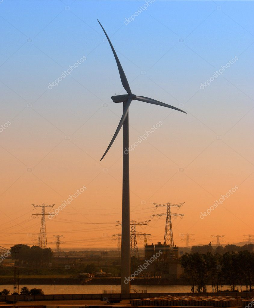 Wind generator at dusk with electricy pylons in background — Stock Photo #2577955