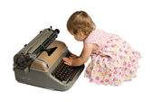 Baby Girl Typing on a Typewriter — Stockfoto