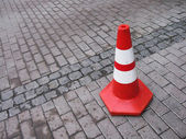 A traffic cone on a cobbled road — Stock Photo