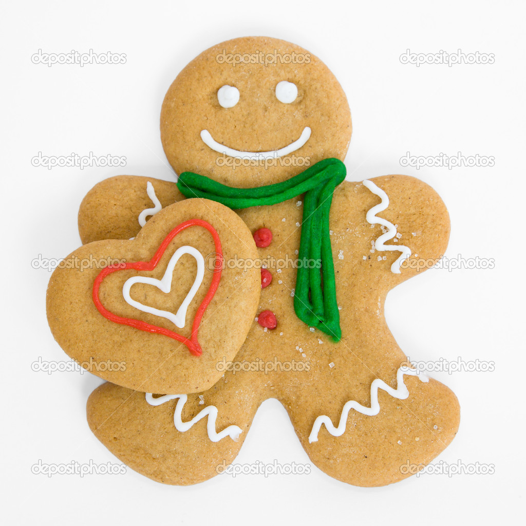 Smiling gingerbread man holds iced gingerbread heart — Stock Photo #2059830