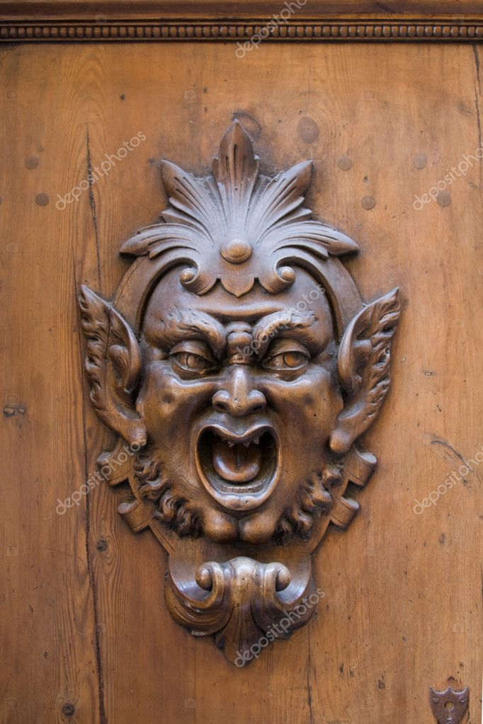 Carved gargoyle adorning a wooden door in Siena, Italy — Stock Photo #2201655