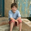 Smiling boy sitting on steps — Stock Photo