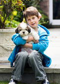 Young boy holding a lhasa apso puppy — Stock Photo