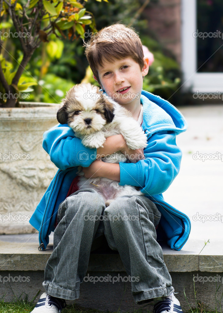 Young boy holding a lhasa apso puppy - Stock Image