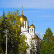 Orthodox church among turning trees — Stok fotoğraf
