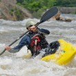 Kayaker fighting the rapids of a river. - Stock Photo