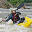 Stock Photo: Kayaker fighting the rapids of a river.