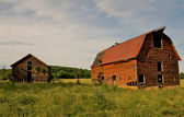 Two old abandoned barns in the country. — Stock Photo