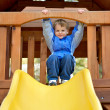 Young boy on a sliding board. - Stock Photo