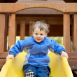 Royalty-Free Stock Photo: Young boy on a sliding board.